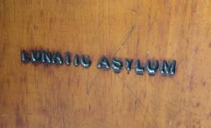 Lunatic Asylum Etching in Woodwork in Utica